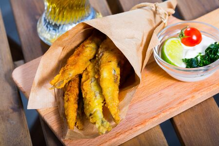 Fish chips - fried in batter anchovies with classic creamy cheese sauce and greens