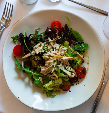Image of tasty chicken salad with arugula and tomatoes at plate Banco de Imagens
