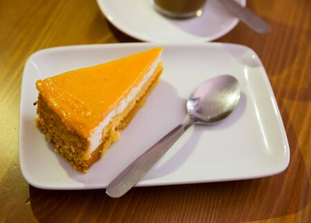 Tender creamy orange mousse cheesecake on white plate