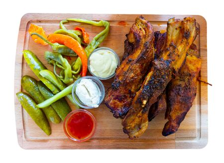 Popular czech grilled pork ribs (Pecena veprova zebra) with three sauces and pickled vegetables. Isolated over white background Stock Photo