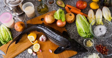 Raw uncooked fish sturgeon at plate before preparing with vegetable on table Banque d'images