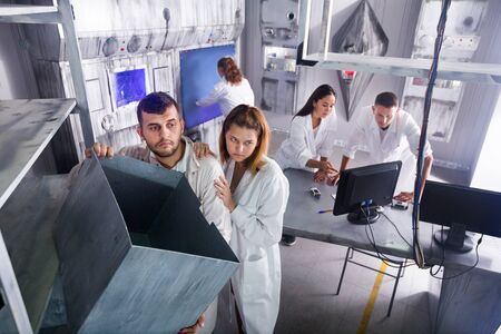 Group of adults in play trying to get out of the escape room stylized under the laboratory Stock Photo
