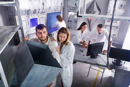 Gruppe von Erwachsenen im Spiel, die versuchen, aus dem Escape Room zu entkommen, der unter dem Labor stilisiert ist Standard-Bild