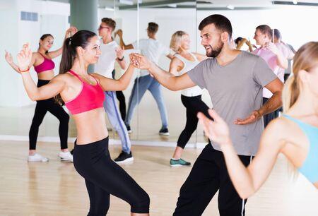 Young positive men and women dancing swing in dance hall