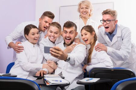 Group of happy medical students and female professor taking selfie in auditorium
