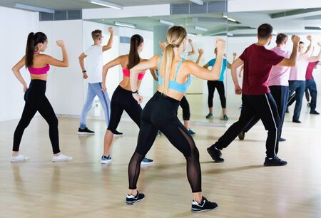 Cheerful positive smiling men women performing modern dance in fitness studio