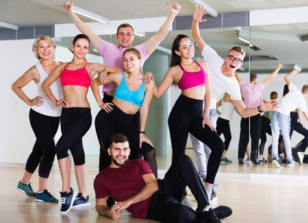 smiling people of different ages posing in fitness studio Foto de archivo