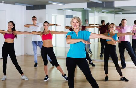 Happy different ages people learning swing steps at dance class and smiling
