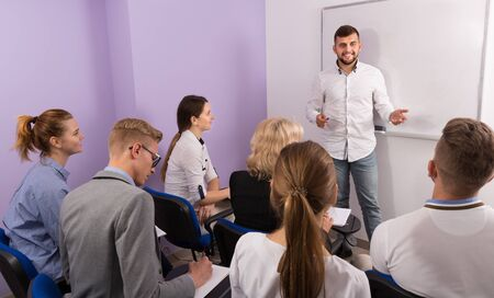 Smiling male student answering near whiteboard in front group of students in auditorium