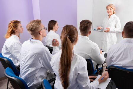 Group of happy  cheerful positive smiling medical students attentively listening to lecture of female teacher in classroom