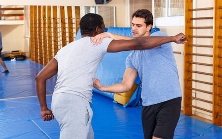 Men practicing effective techniques of self-defence during individual class in training room