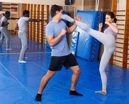 Erwachsene Menschen, die im Schulungsraum effektive Selbstverteidigungstechniken praktizieren
