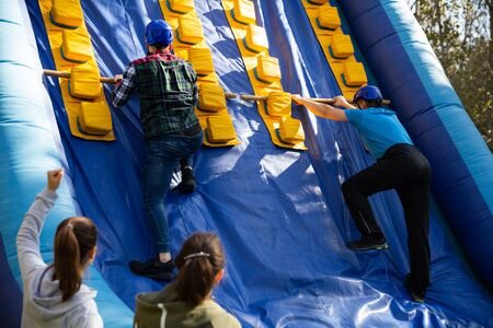 Happy friends enjoying a day at amusement park, climbing on inflatable slide with wooden poles