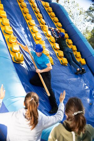 Man competing with his friend in climbing on tall inflatable slide with wooden sticks on adults bouncy playground