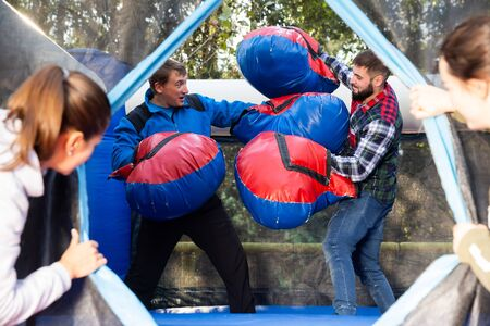 Two men in big boxing gloves boxing on inflatable ring in outdoor amusement park