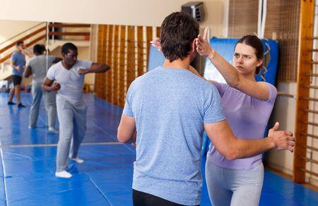 Mujer y hombre practicando técnicas de autodefensa en el gimnasio