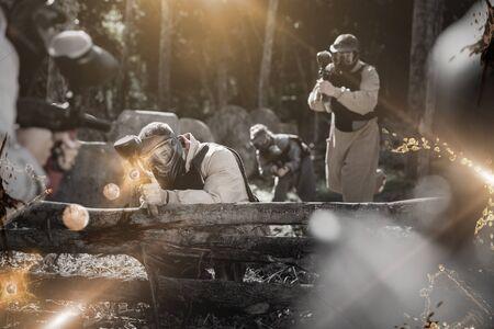 Portrait d'une équipe d'adultes jouant sur un champ de bataille de paintball en plein air, image avec effets lumineux et flou Banque d'images