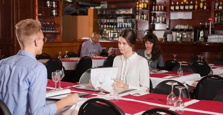 Elegant young woman sitting with menu at table in restaurant, communicating with male friend