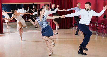 Happy dancing couples enjoying active swing in modern studio Stock Photo