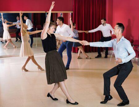 Happy cheerful positive dancing couples enjoying active swing in modern studio