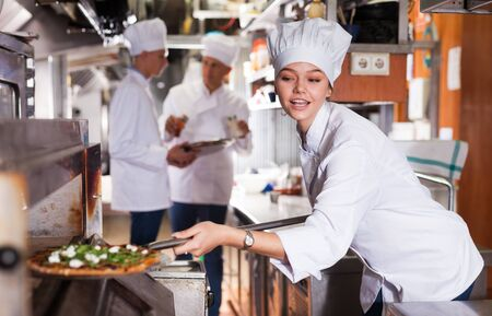 Attractive female chef of restaurant working in professional kitchen, baking ordered pizza
