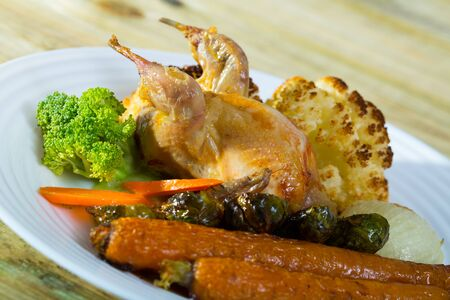 Delicious roasted whole quail served with assorted baked vegetables and honey-mustard sauce