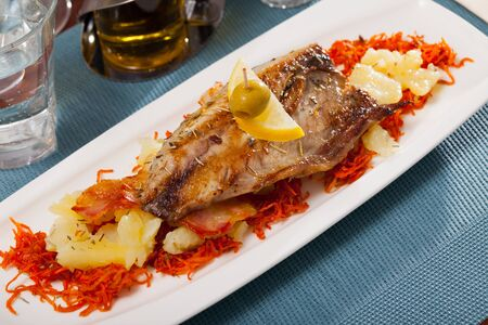 Grilled mackerel fillet served with baked potatoes, carrots and slice of lemon Stok Fotoğraf