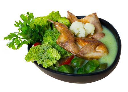 Cream soup  with quails,  broccoli,  brussels sprouts and cauliflower at bowl.  Isolated over white background Banco de Imagens