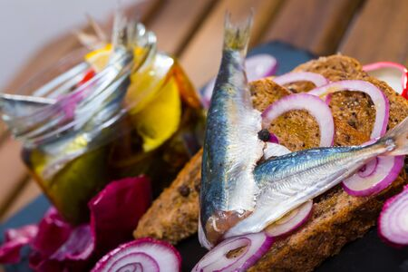 Homemade pickled sprats with onions, beets, mix of peppers and marinade of vinegar, lemon, olive oil and sea salt. Served on rye bread with onion Stok Fotoğraf