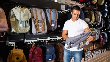 Positive glad cheerful  smiling man choosing backpack in streetwear store