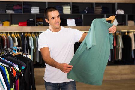 Positive male customer choosing t-shirt in showroom