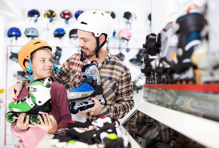 Smiling father and his son examining various a roller-skates in the sports store. Focus on both persons Stok Fotoğraf