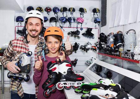 Young  cheerful positive father and son showing roller-skates they bought in sports store