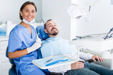 Mężczyzna siedzi zadowolony na krześle po zabiegu w gabinecie stomatologicznym