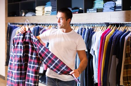 Man chooses fashionable checkered shirt in the fashion store