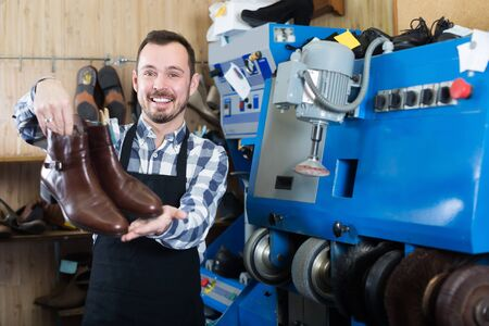 Cheerful male worker showing fixed shoes in shoe repair workshop