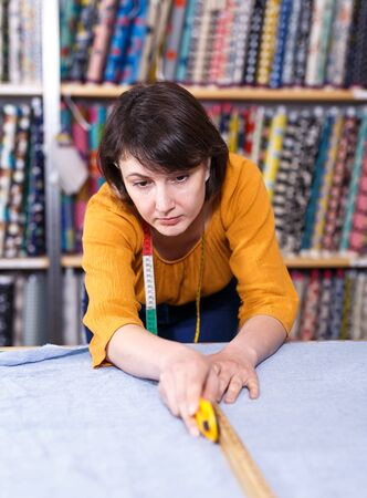 Focused saleswoman working in fabric store, measuring and cutting off piece of cloth to order 免版税图像