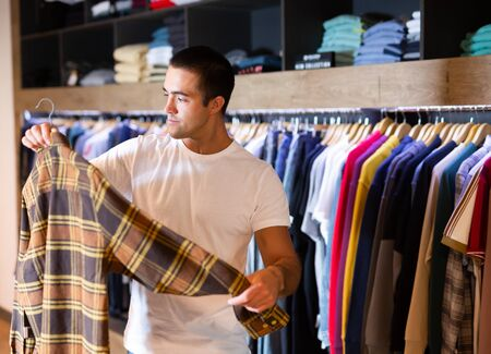 Man buys checkered shirt in the fashion store