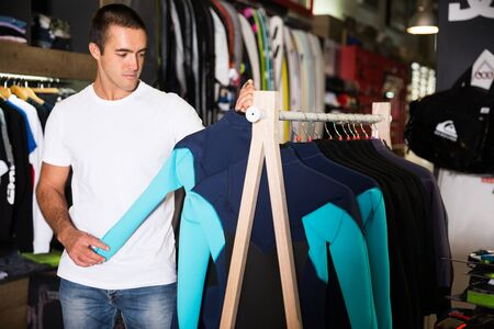Young male chooses sportswear in a clothes store Zdjęcie Seryjne