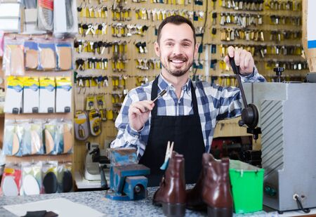 happy russian  male worker showing key he made in repair workshop Stok Fotoğraf