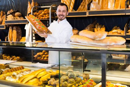 Smiling assistant demonstrating delicious festive cake in bakery Imagens