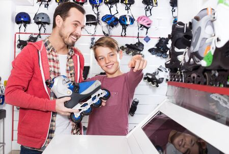 Smiling father and son examining various roller-skates in the sports store. Focus on child