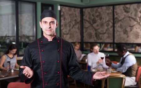 Confident male chef welcoming to visit cozy restaurant