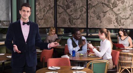 Handsome elegant waiter standing with welcome gesture in restaurant hall