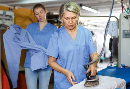 Two female cleaning services salon employees in process of ironing clean clothes