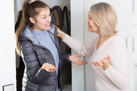 Mature woman saying goodbye her adult daughter in entrance hall of apartment