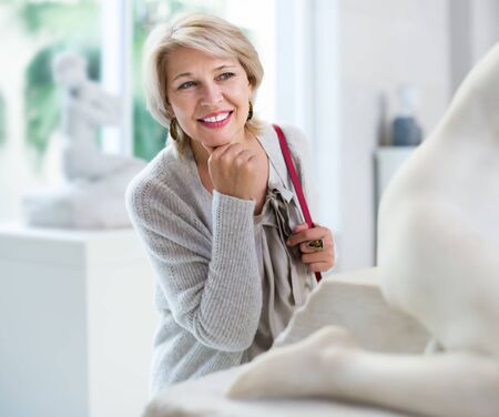 Portrait of positive mature woman visitor near sculpture in the historical center