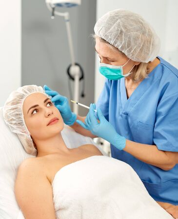 Portrait of woman during beauty facial injections in medical esthetic office Stock fotó