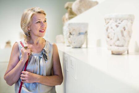 Mature woman standing in art center near antique sculpture