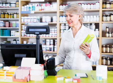 Aged woman seller is checking assortment of care products in store. Stock Photo